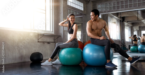 Fotografia  Smilling Muscular Asian couple rest after work out while sitting on yoga ball at the gym