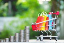 Stack Of Coins With Colorful Paper Shopping Bags In A Trolley Or Shopping Cart,E-commerce Concept.