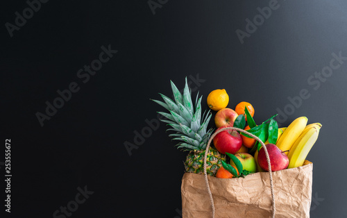 fresh healthy organic fruits bought on weekly market in brown paper bag against dark table background