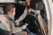 Mother securing her toddler daughter buckled into her baby car seat from the front seat