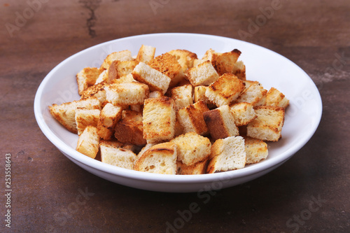 Fotografía  Delicious crispy croutons, crumbs of bread in white plate