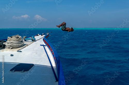 malediwski mężczyzna skaczący w wodzie i nurkujący z łodzi