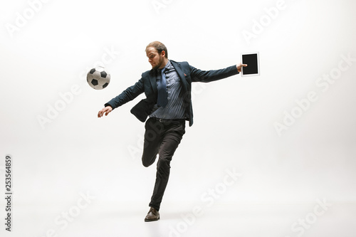 Carta da parati Businessman with tablet and football ball in office
