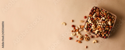 Fotografia, Obraz Dried fruits and nuts mix in a wooden bowl.