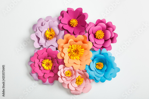 top view of colorful paper flowers on grey background