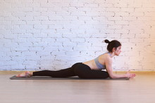 The Girl Is A Professional Instructor Of Hatha Yoga Practicing Asanas In The Room Against The Background Of A White Brick Wall. Eka Pada Rajakapotasana Variation (King Pigeon Pose).
