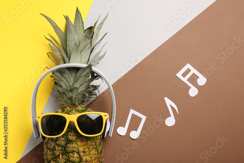 Funny pineapple with headphones and sunglasses on color background, flat lay - 253584290