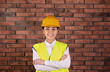 Female industrial engineer in uniform on brick wall background. Safety equipment