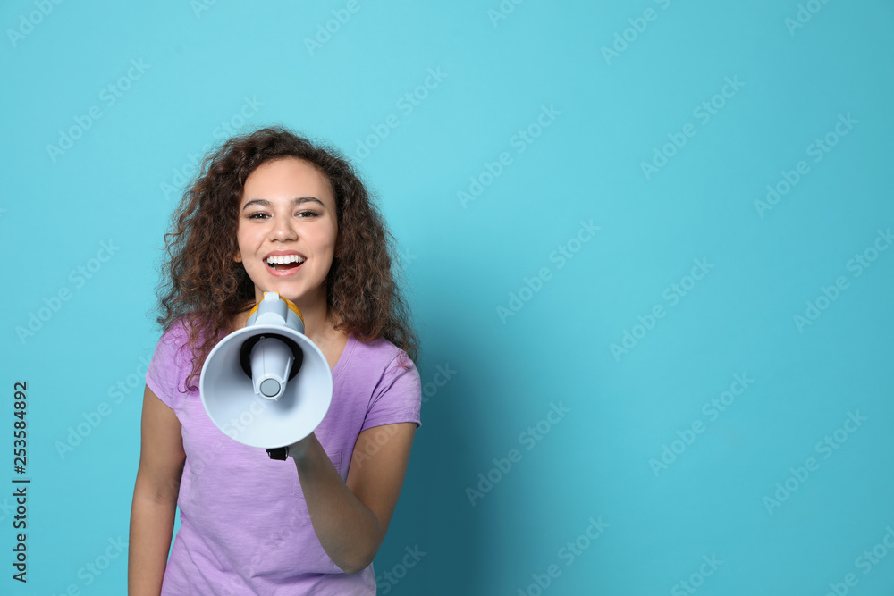 Fototapeta Young African-American woman with megaphone on color background. Space for text