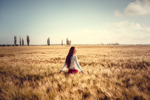 Young Woman Standing On A Wheat Field