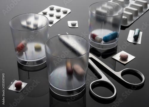 Fotografia  Dosage glasses medication next to scissors, conceptual image, horizontal composi