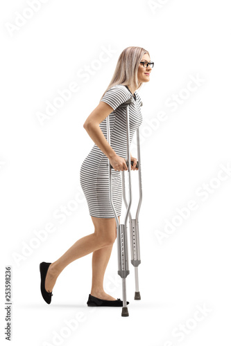 Young woman walking with crutches Poster Mural XXL