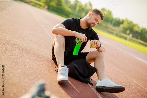 Fotografie, Obraz  Sporty young man sitting on stadium track and looking at wrist watch