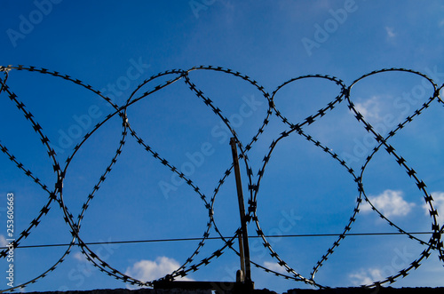 Fotografía  Metal barbed wire on a blue sky with white clouds
