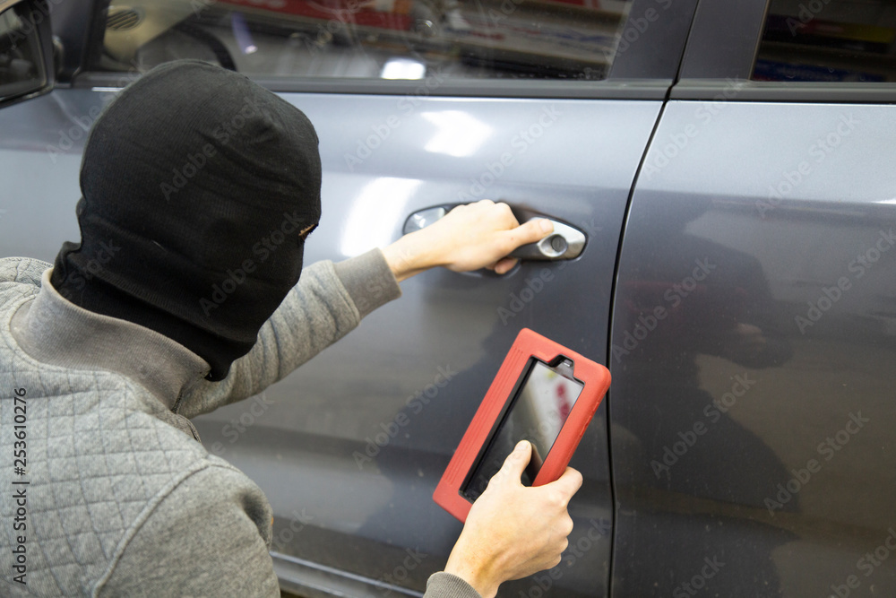Fototapeta The hijacker tries to break into the car with a scanner. Code grabber . Car thief, car theft.