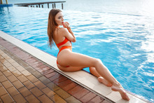 Elegant Sexy Woman In The Orange Bikini On The Sun-tanned Slim And Shapely Body Is Posing Near The Swimming Pool