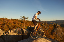 Professional Cyclist Balancing On Back Wheel On Trial Bicycle. Young Sportsman Making Acrobatic Stunt On The Edge Of Big Boulder On The Top Of Mountain. Concept Of Extreme Sport Active Lifestyle