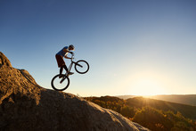 Silhouette Of Professional Cyclist Riding On Back Wheel On Trial Bike. Fearless Sportsman Biker Making Acrobatic Stunt On The Edge Of Big Boulder At Sunset. Concept Of Extreme Sport Active Lifestyle