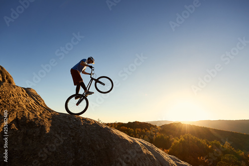 Silhouette of professional cyclist riding on back wheel on trial bike Принти на полотні