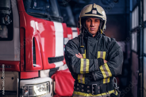 Photo Confident fireman wearing protective uniform standing next to a fire engine in a