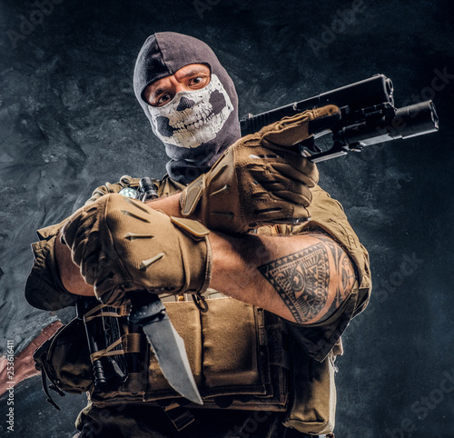 Fotografia A terrorist in a military uniform and a skull balaclava holding a pistol and a knife and looks at the camera with a menacing look