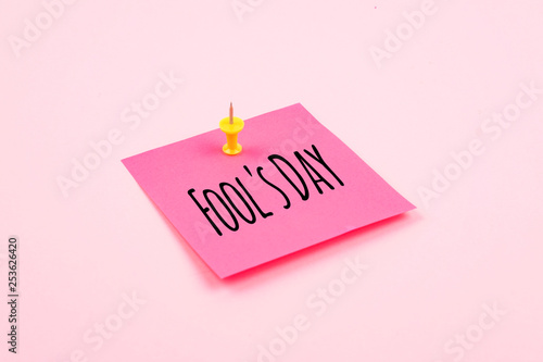 Fotografie, Obraz  April Fools' Day text celebration background with paper sticky note and office pin on pink background