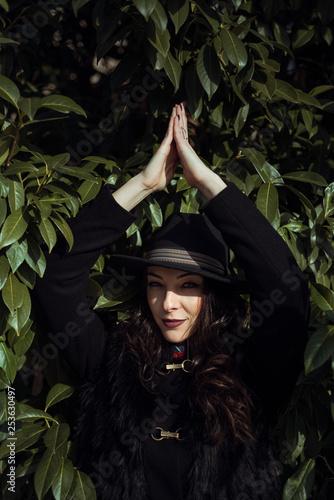 Fotografie, Tablou  Brunette posing in front of a huge bush