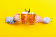 canvas print picture - two glasses of beer in the hands ,clink glasses on a yellow background