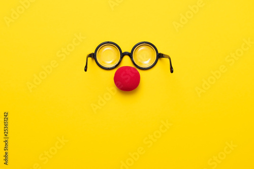 Fotografie, Obraz Funny glasses, red clown nose and tie lie on a colored background, like a face