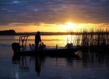 Unrecognizable Fisherman Moves His Boat Into Position As The Sun Comes Up