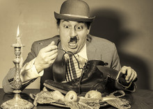 Poverty Stricken, Bankrupt, Poor Caucasian Male With Mustache ,eating A Boot By Candle Light , In A Dirty Room ,dressed As Charlie Chaplin Type Character ,wearing A Hat.