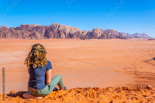 Fotomural A lonely girl is observing Wadi Rum desert in Jordan from a hilltop