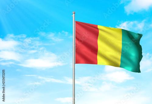 Fotografía  Guinea flag waving sky background 3D illustration