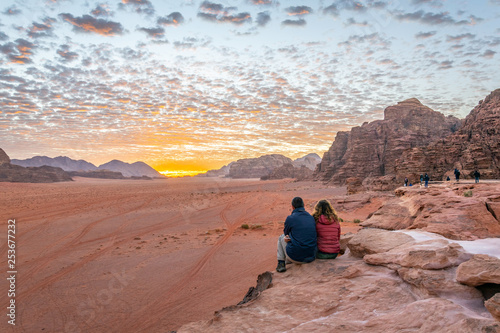 Photo  A young couple is watching at sunrise over wadi rum desert in Jordan
