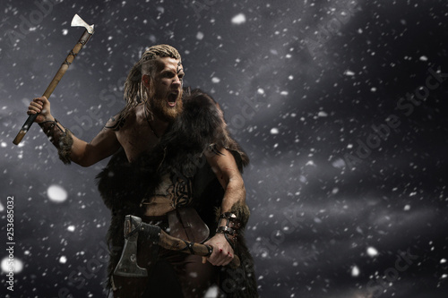 Photo  Medieval warrior berserk Viking with tattoo and in skin with axes attacks enemy