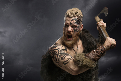 Foto  Medieval warrior berserk Viking with tattoo and in skin with axe attacks enemy