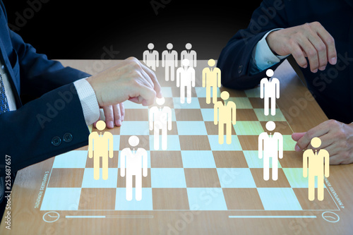 Three business administrators playing checkers or draughts on a wooden virtual checkerboad or draughtboard in concept of manpower or human resource strategy planning to form a teamwork Canvas Print