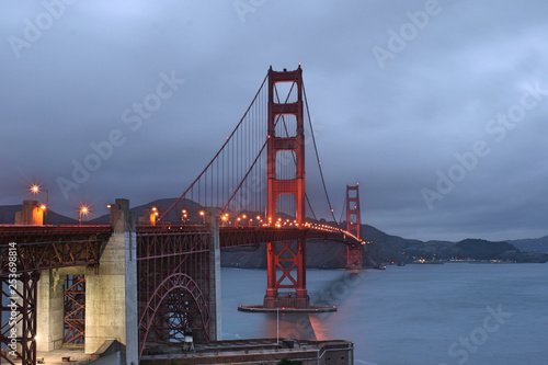Aluminium Prints Golden gate bridge with streetlights and hills in background on cloudy evening