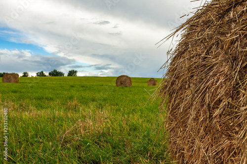 Valokuva  A stack of straw against the background of a field of blue sky and the rays of t