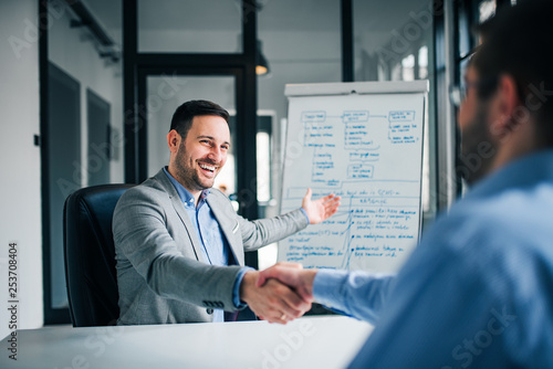 Fototapety, obrazy: Smiling millennial businessman handshaking coworker, celebrating successful teamwork.