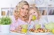 Portrait of grandmother and granddaughter having breakfast