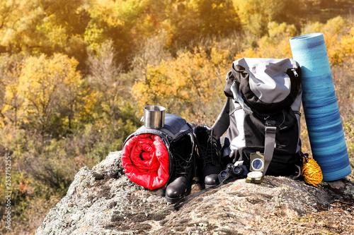 Fotografiet  Set of camping equipment with sleeping bag on rock outdoors