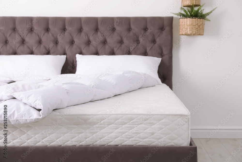 Fototapeta Comfortable bed with new mattress in room. Healthy sleep