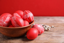 Wooden Bowl With Red Painted Easter Eggs On Table Against Color Background, Space For Text