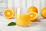 Glass with orange juice and fresh fruit on table