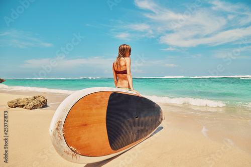 Fotografie, Obraz  Beautiful surfer girl in bikini with surfboard enjoying on the beach