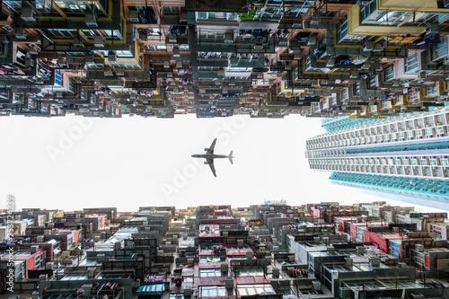 Foto auf AluDibond Grau Airliner bei der Landung über Hochhäusern