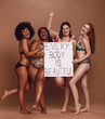 Cheerful female group with every body is beautiful signboard