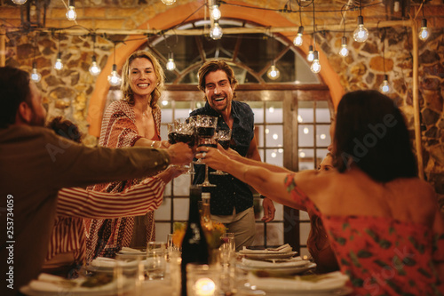 Fotografia Host couple toasting drinks with guest at party