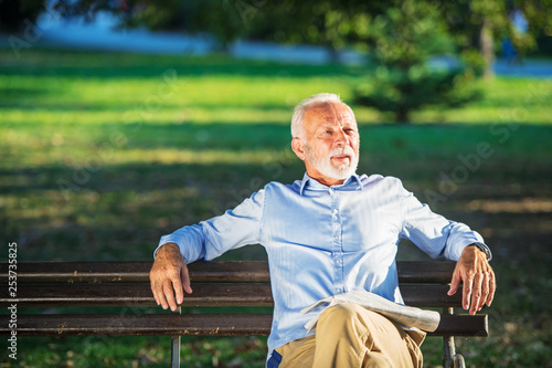 Senior man relaxing in park on a sunny day seated on a wooden bench and waiting Canvas-taulu